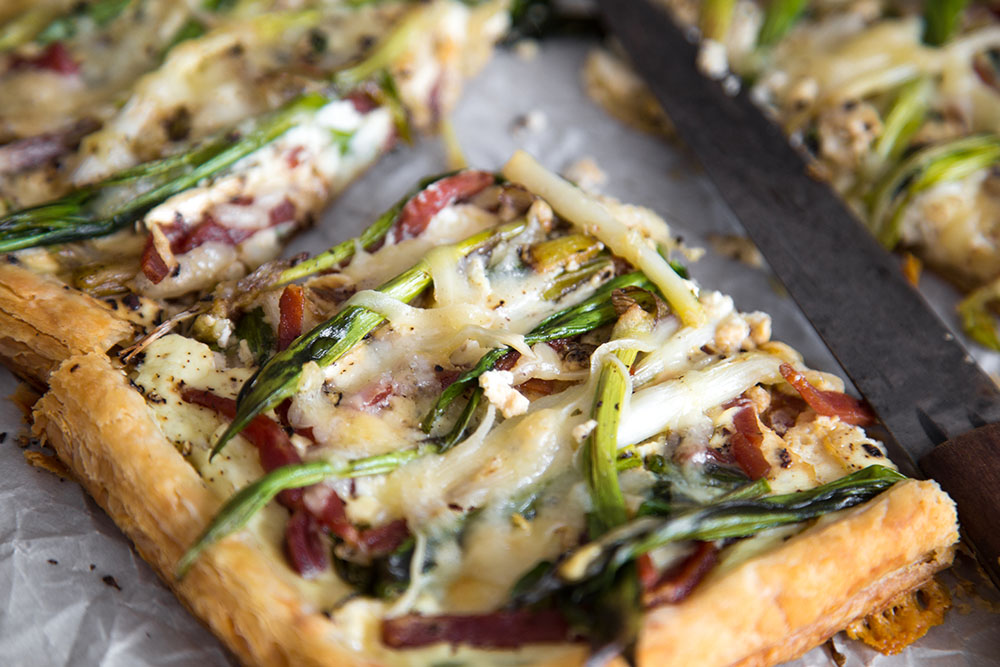 close up of a cooked ramp tart, ramp tart with country ham, ramp tart on puff pastry
