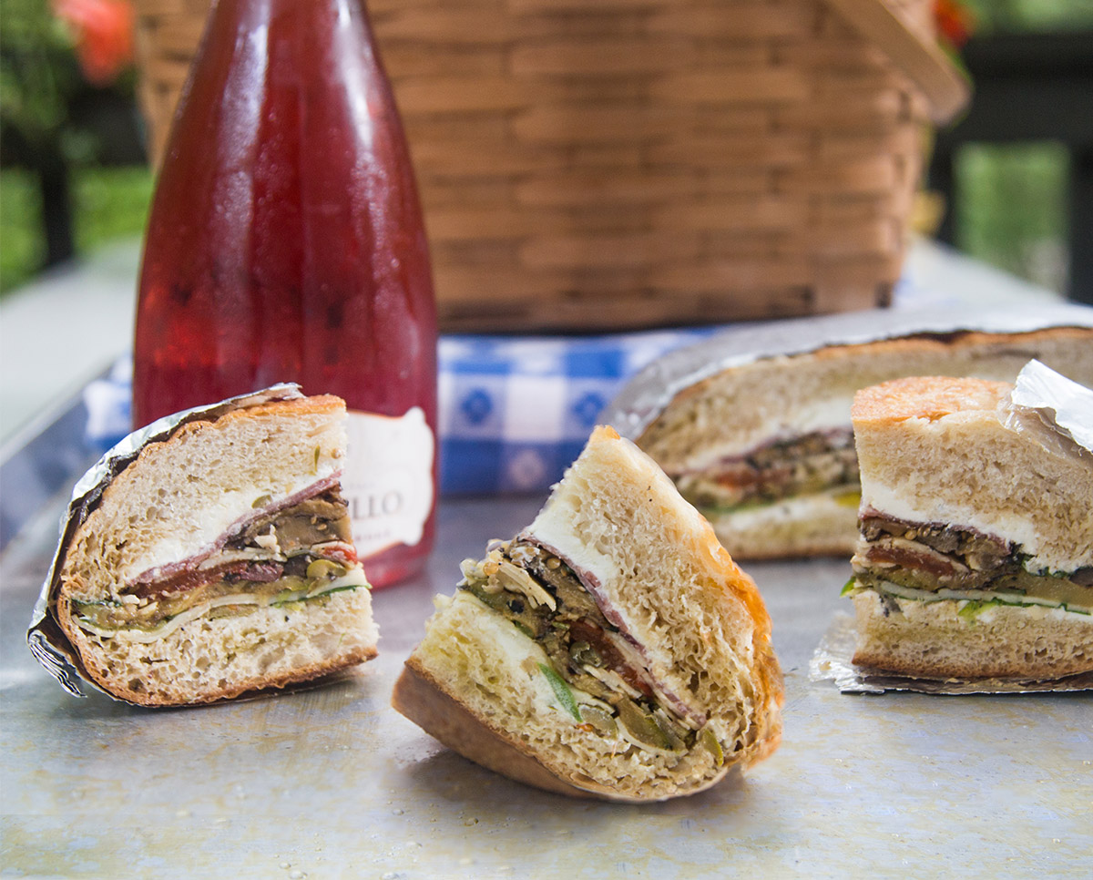 pressed picnic sandwich slices, a wine bottle, a picnic basket